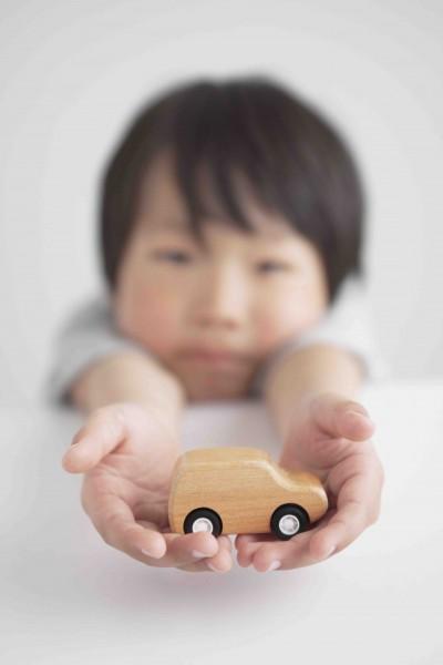 木製の車のおもちゃを持つ男の子